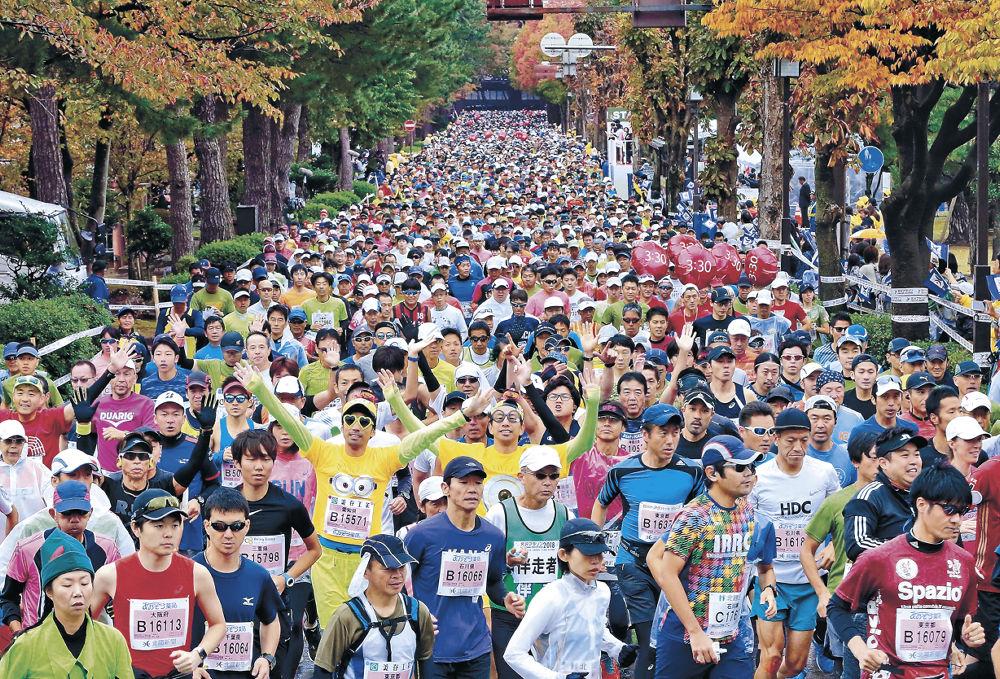 木々が色付く広坂通りを駆け抜けるランナー=金沢市広坂1丁目
