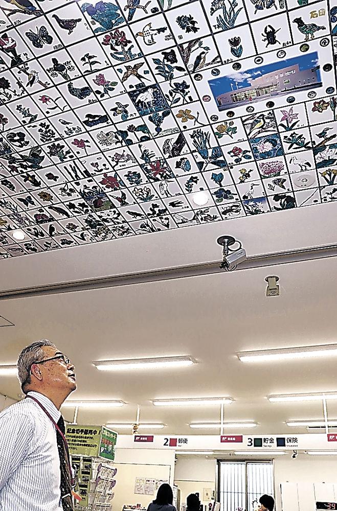 新庁舎の天井に飾られた写真に見入る利用者=能美市寺井町の寺井郵便局