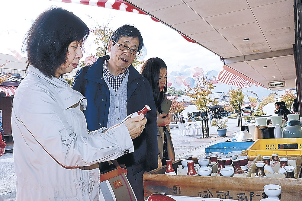 お気に入りの九谷焼を品定めする来場者=能美市泉台町の九谷陶芸村