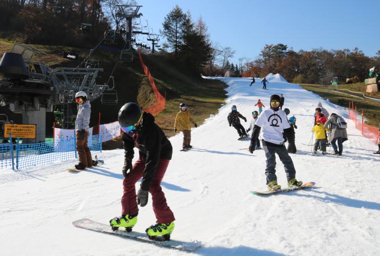紅葉も楽しめるゲレンデで初滑走を楽しむ来場者ら=3日午前9時14分、軽井沢町