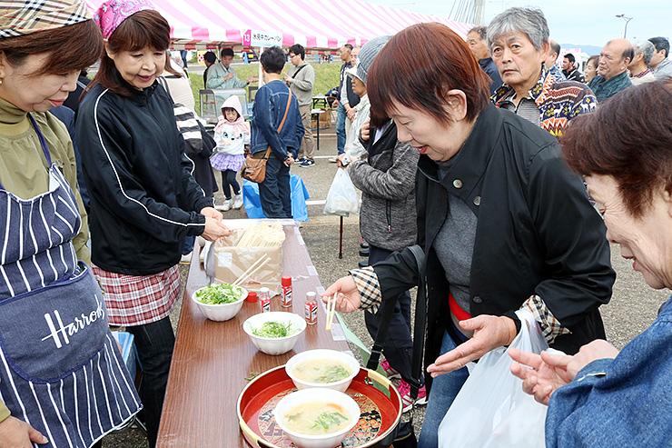 食を楽しみに来た大勢の人でにぎわうひみ食彩まつり=氷見市漁業文化交流センター前