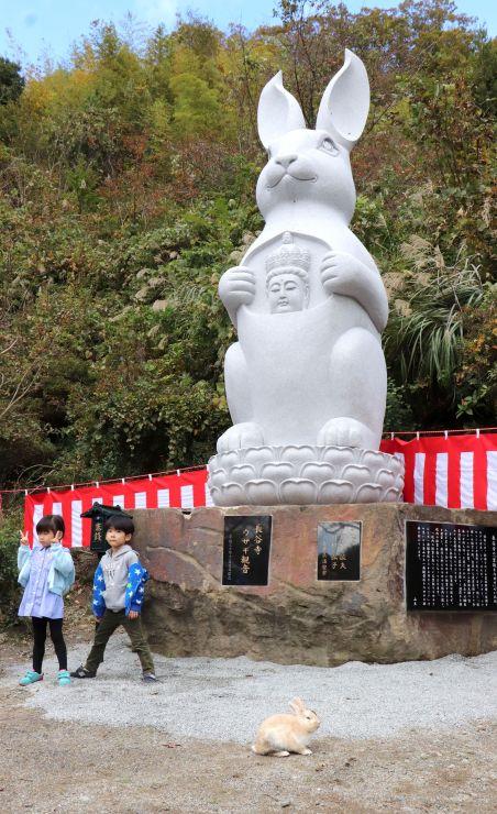除幕式でお披露目された高さ約6メートルのウサギ観音。手前は「草取りウサギ」=3日、佐渡市