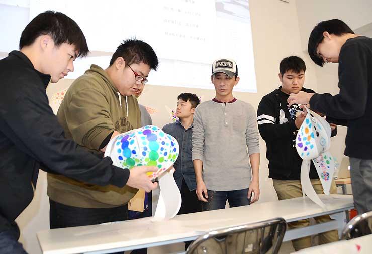ランタンの組み立て方を堤さん(右から3人目)から教わる長野美専の生徒たち