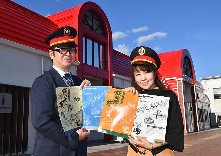 JR飯田駅前でクリアファイルを手にする実行委の尾沢さん(左)と熊谷さん