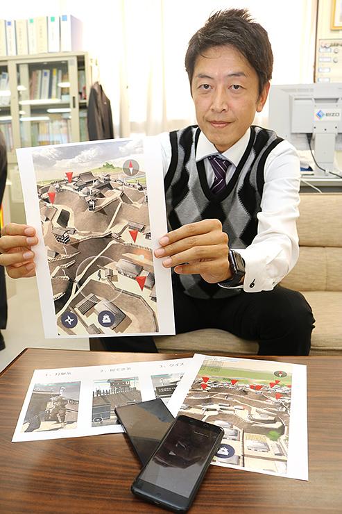 アプリのイメージ画像を持つ野原さん=砺波市役所庄川支所