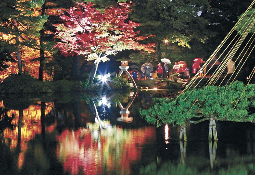 ライトアップされた紅葉や霞ケ池に映った幻想的な光景を楽しむ来園者=兼六園