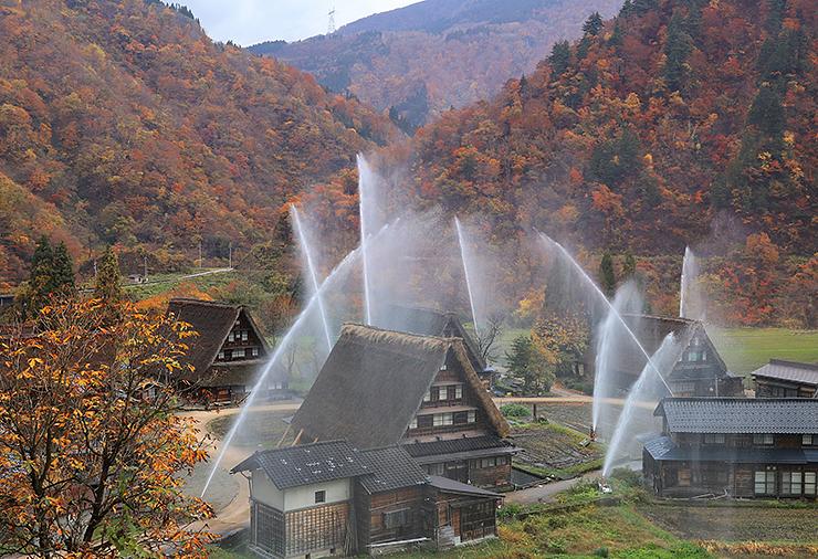 周囲の山々の紅葉が鮮やかな合掌造り集落で行われた消防訓練=南砺市菅沼