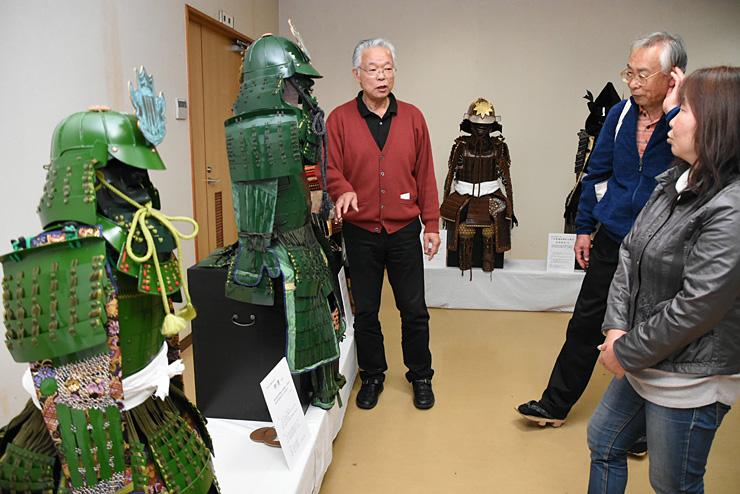 来場者に松本山雅FCにちなんだ緑色の甲冑などを説明する赤広さん(左)