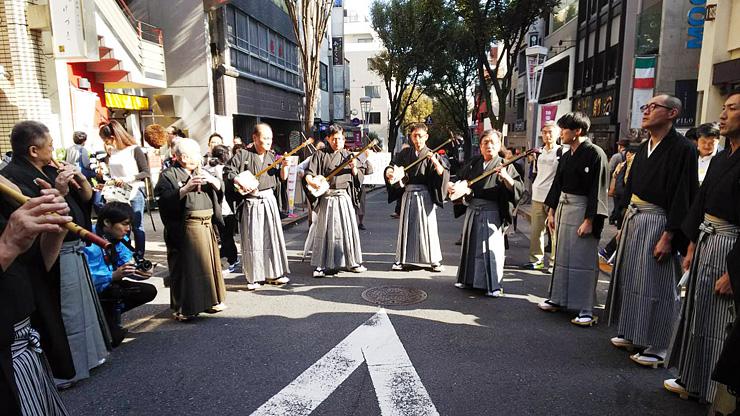 大勢の観光客が見守る中、しっとりと庵唄を響かせる宝槌会のメンバー=東京・神楽坂