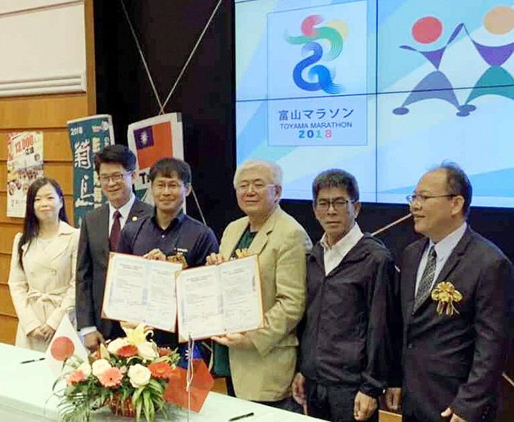 澎湖跨海マラソンの企画メンバーとともに覚書に調印した片岡課長(左から3人目)=台湾・澎湖島