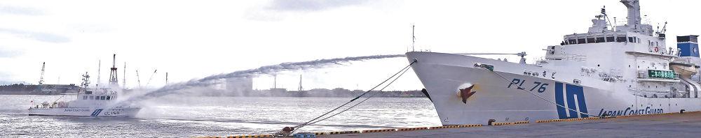 外国漁船を想定した船(左)に放水する大型巡視船「さど」=金沢港五郎島岸壁