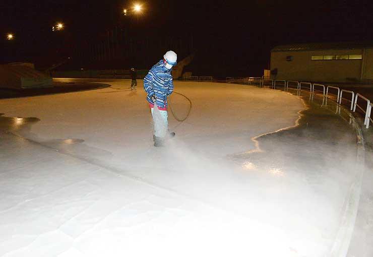 やまびこ国際スケートセンターの今季開業を前に、リンクに湯をまいて製氷するスタッフ
