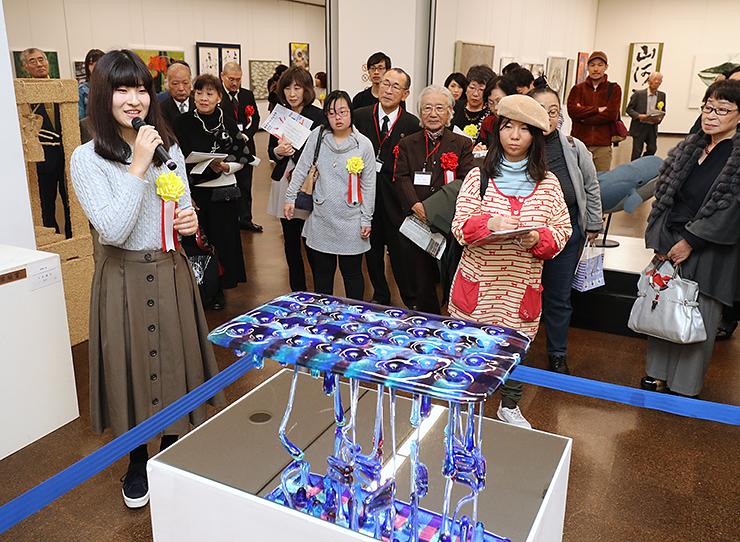 立体部門で大賞に選ばれた小松さん(左)の説明を聞きながら、作品を鑑賞する美術ファン=県民会館