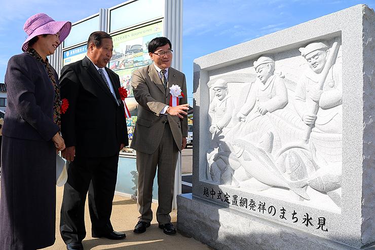 設置されたモニュメントを眺める林市長(右)と寄贈者の内生蔵さん夫妻=JR氷見駅前