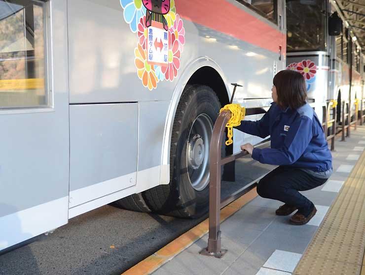 運行直前にトロリーバスのタイヤを確認する運転士