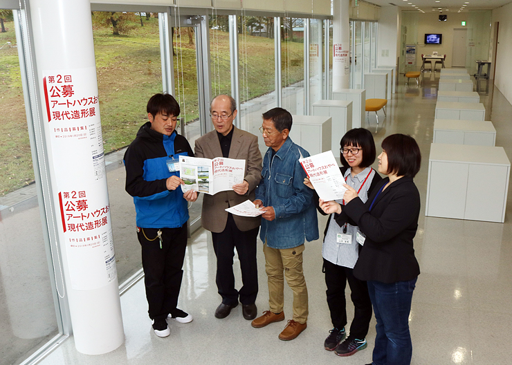 募集パンフレットを手に打ち合わせする埴生さん(左から2人目)ら実行委メンバー=アートハウスおやべ