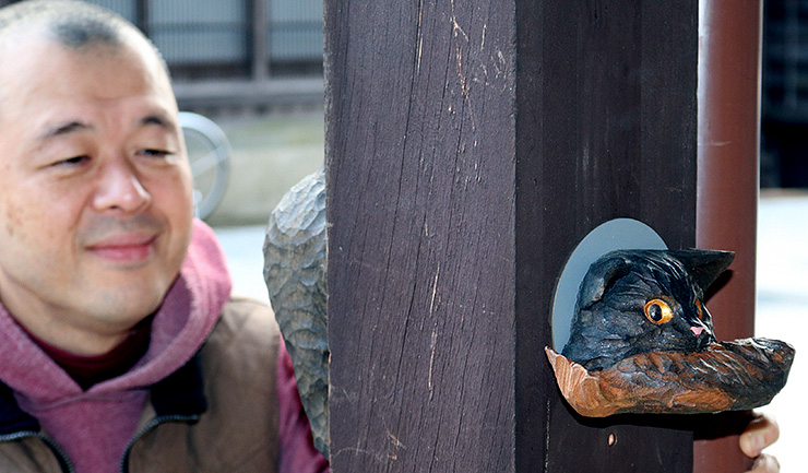 イワナをくわえ、柱から抜け出そうとしているように見える木彫ネコ=南砺市井波