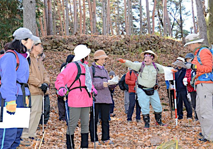 林城跡の小城の石積み(奥)を見学する参加者