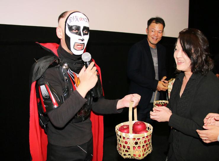 舞台あいさつ後に来場者から贈られたリンゴを受け取る鉄拳さんと山本監督(中央奥)