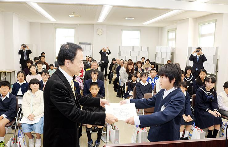 齊藤富山銀行頭取(手前左)から表彰状を受け取る吉田君=富山銀行本店