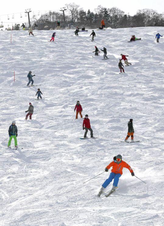 初滑りを楽しむスキーヤーやスノーボーダー=24日、湯沢町