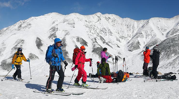 白銀の立山連峰の景色を楽しみながらスキーで散策する人たち=立山・雷鳥荘前