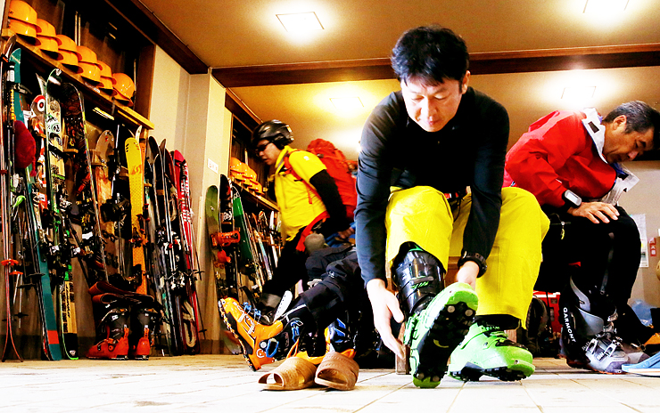 スキーブーツを履く宿泊者。左側にスキー板やスノーボードがずらりと並ぶ=雷鳥荘