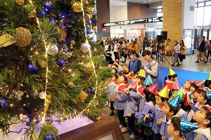 クリスマスツリーを見上げる園児=富山駅南北自由通路