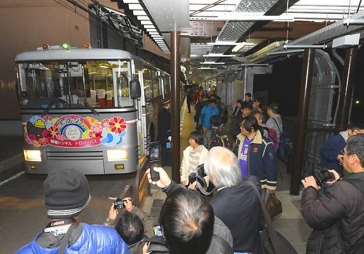 運行を終た関電トンネルトロリーバスの最終便。乗客が別れを惜しんで写真に収めていた=30日午後4時51分、大町市の扇沢駅