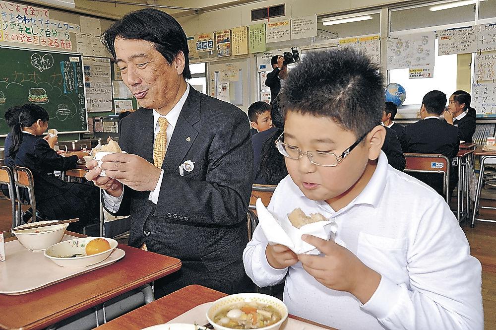 ごはんば~がを味わう児童と井出市長(手前左)=能美市宮竹小