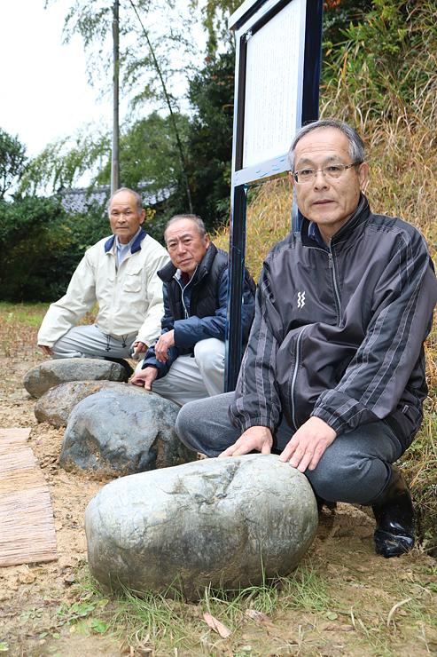 八幡社の境内に展示した盤持石を紹介する山崎会長(右)