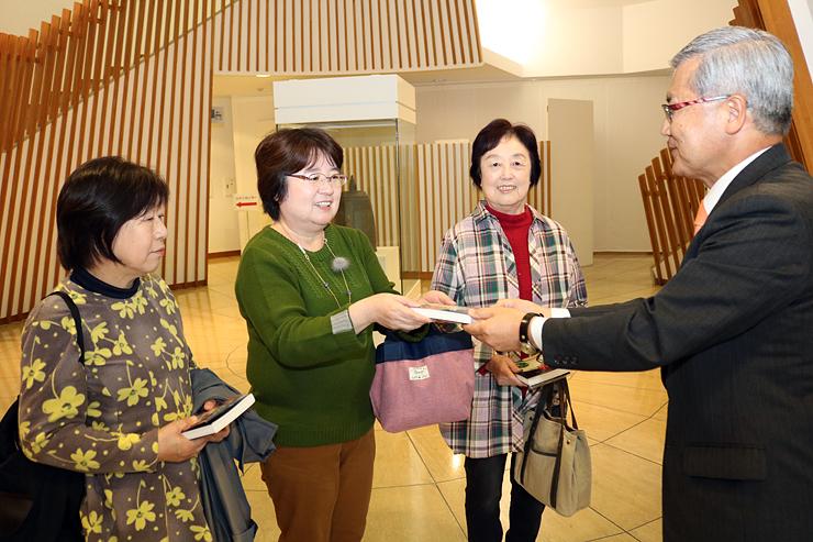 1万人目の記念品を受け取る水口薫さん(左から2人目)と前後に来場した水口マサヱさん(同3人目)、山口さん(左端)