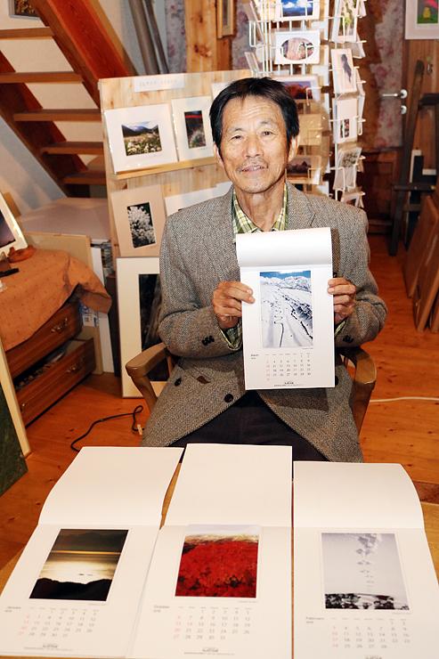 立山連峰を題材にしたカレンダーを手にする高橋さん