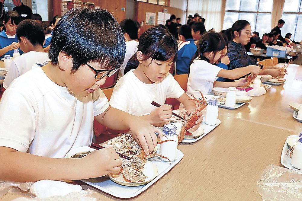 慣れた手つきで地物のコウバコガニを食べる児童=加賀市橋立小中