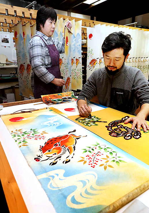 一枚一枚、丁寧に手染めし、えとの和紙タペストリーを作る石本さん(右)=五箇山和紙の里