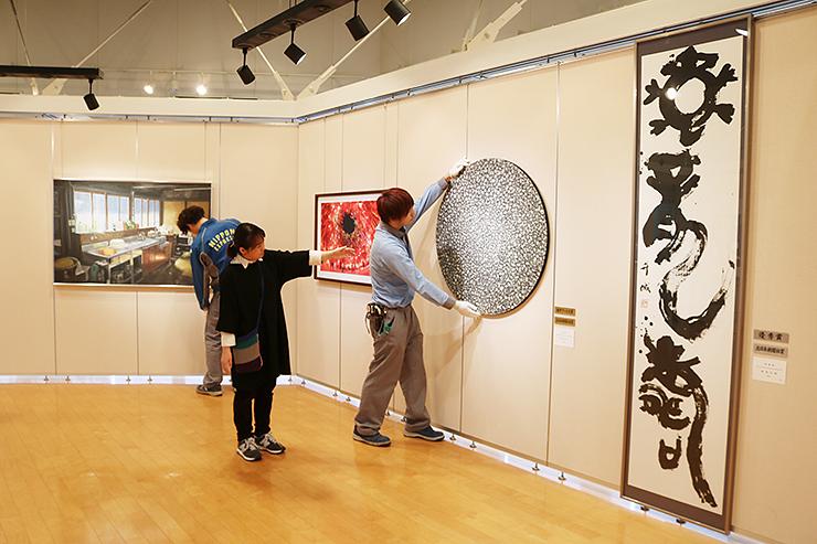 麻生さん(左から2人目)の指導で作品を展示するスタッフ=北日本新聞砺波支社ギャラリー