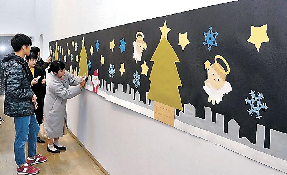 来館者が切り絵の雪の結晶を貼り付ける壁画を準備する金沢学院大の学生=加賀市中谷宇吉郎雪の科学館