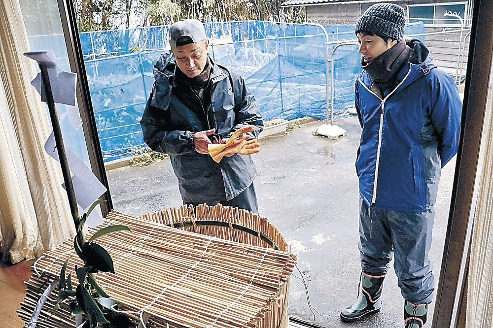 鵜様を収めるかごの前で話し合う小西さん(左)と達矢さん=七尾市鵜浦町