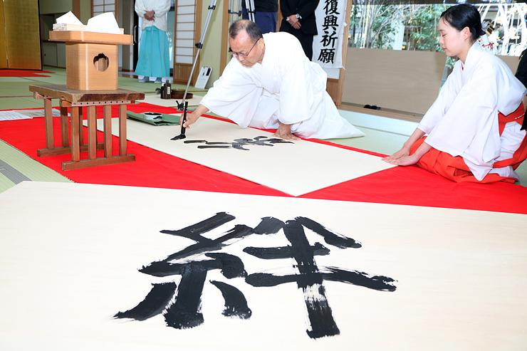 絵馬に筆で文字を書く高尾支部長=射水神社