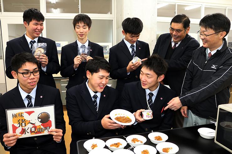 開発したイノシシ肉カレーを手に出来栄えを語り合う氷見高校の生徒ら