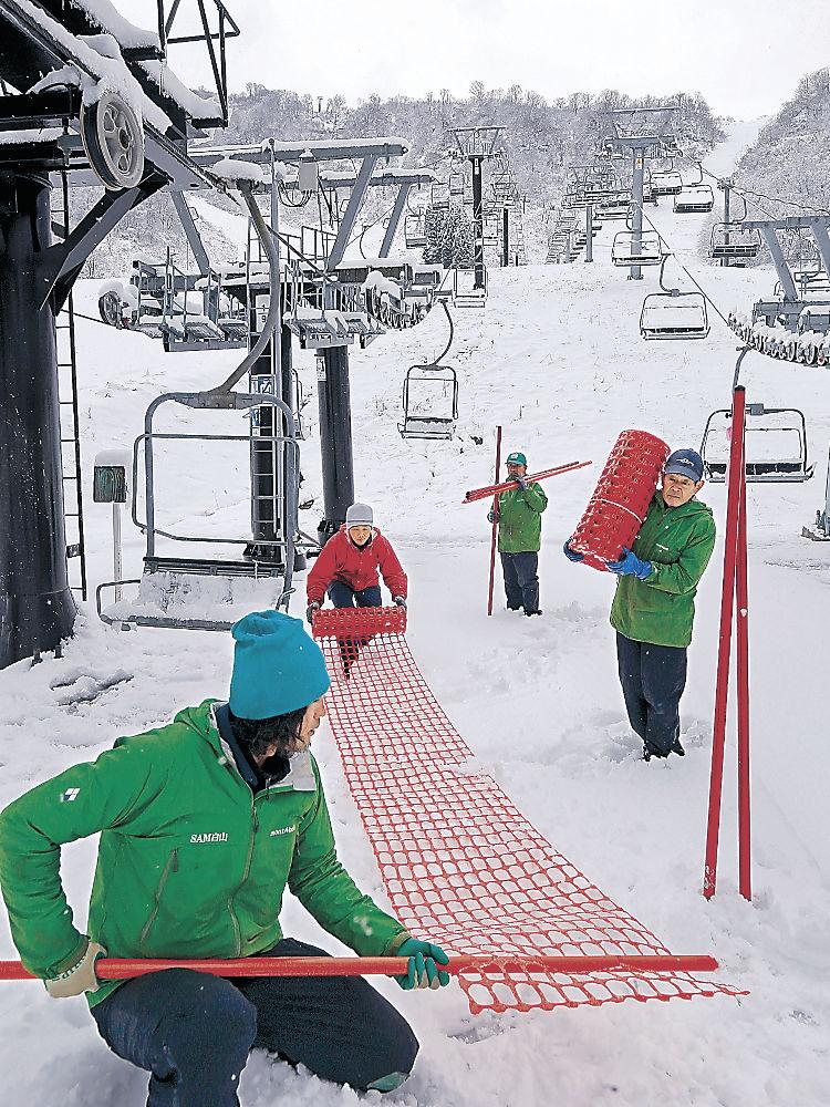 真っ白になったゲレンデでオープンの準備を進める関係者=白山市の白山一里野温泉スキー場