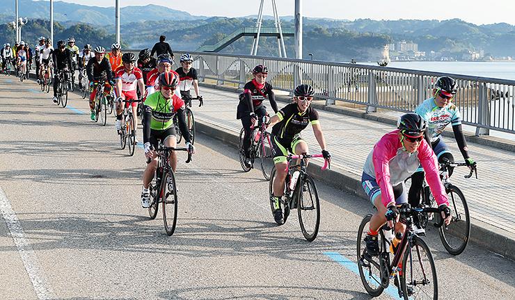 今年の大会で、富山湾の眺めを楽しみながら自転車をこぐ参加者=4月、氷見市の比美乃江大橋