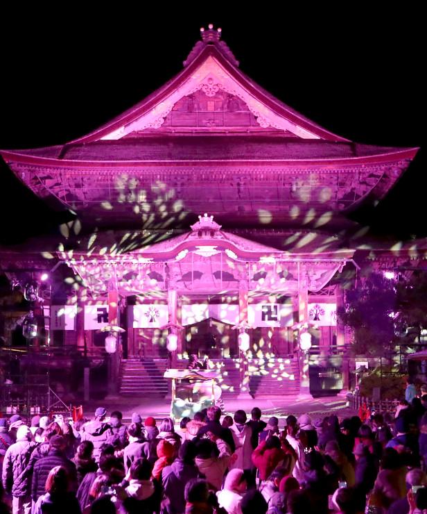 善光寺本堂でのイルミネーション。光の演出を大勢の人たちが楽しんだ=15日午後5時半すぎ、長野市