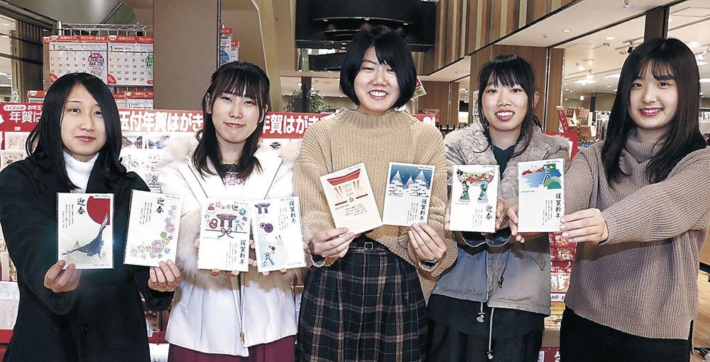 金沢の観光名所などをデザインしたはがきをPRする金沢学院大の学生=市内の書店