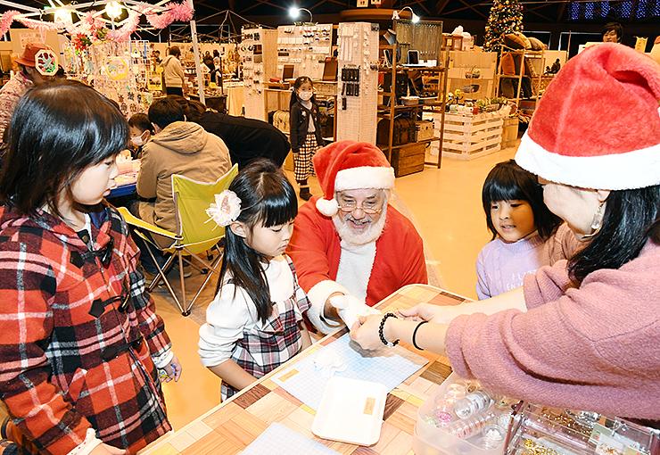 サンタクロースに扮した男性と一緒に雑貨を作る子どもたち=高岡テクノドーム
