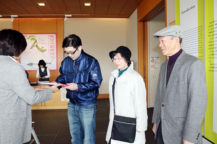 中川館長から記念品を受け取る(左2人目から)平井淳一さん、寿美枝さん、竹雄さん=県水墨美術館