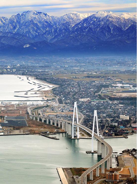 新湊大橋の奥に姿を見せた立山連峰=16日午前11時半ごろ、富山新港上空、本社チャーターヘリから