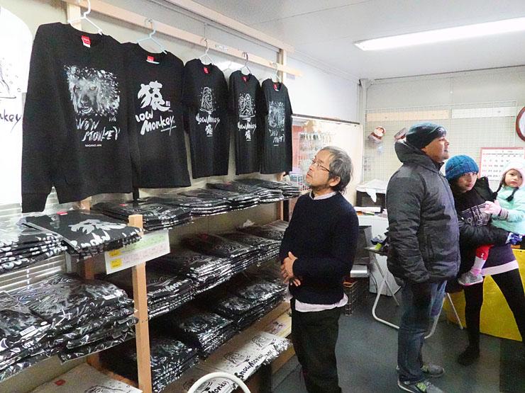 足立さん(左)が描いたスノーモンキーのTシャツなどが並んでいる店内