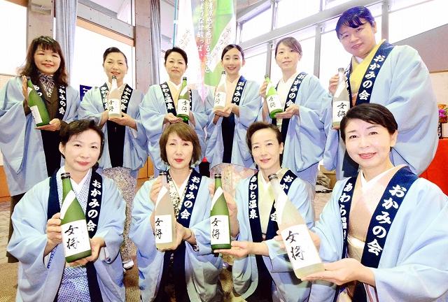 「女将」を手に笑顔を見せるあわら温泉旅館の女将=12月18日、福井県あわら市のセントピアあわら