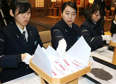 お守りを作るあいの風とやま鉄道の社員=高岡関野神社